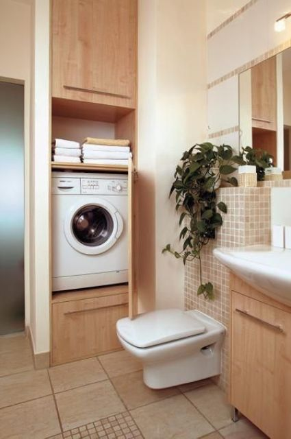 a warm-colored modern bathroom with a washing machine hidden in the wall and covered with doors
