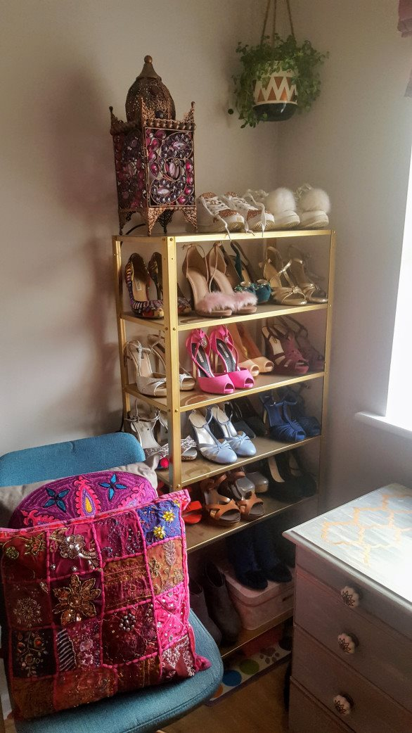 an IKEA Hyllis shelf fully spray painted gold makes up a chic shoe storage unit