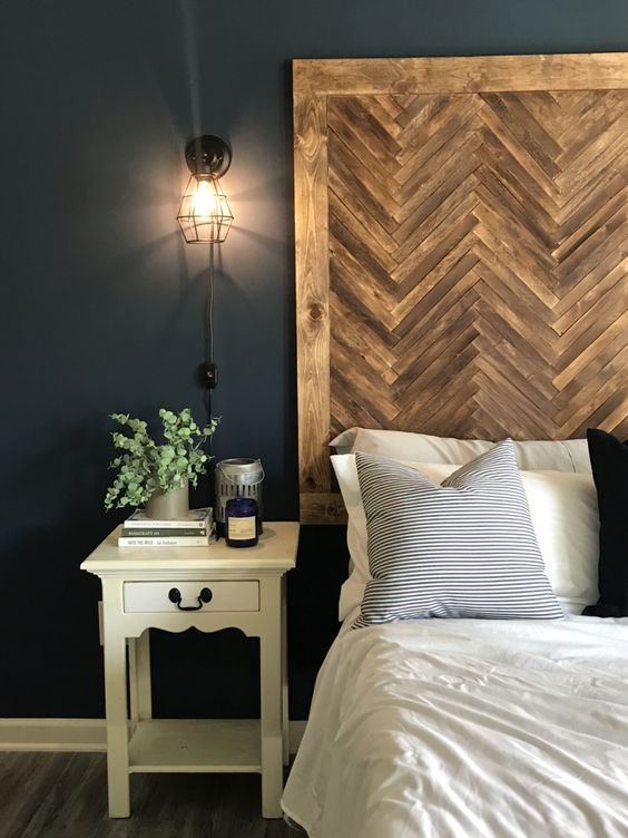 an oversized dark stained herringbone framed wooden headboard is a cozy rustic idea for your bedroom