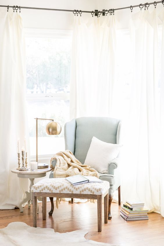 a mint wingback chair, a printed footrest, a side table with a chic metallic table lamp and pillows
