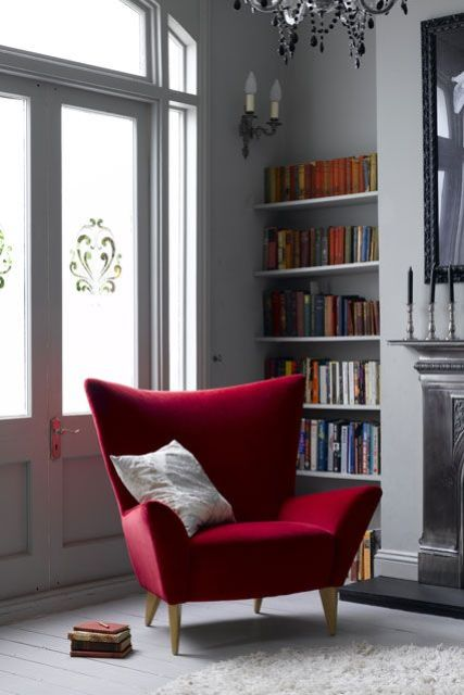 a bold red wingback chair with sharp geometric lines and a pillow is a bright statement for your reading nook