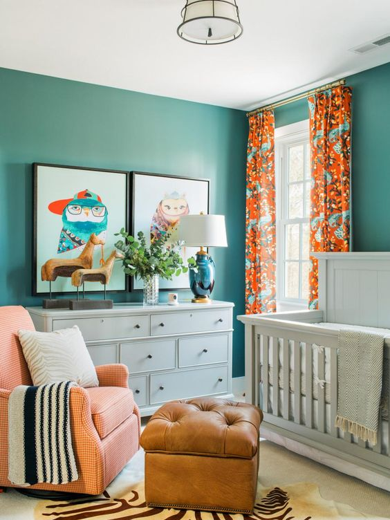 a colorful gender neutral nursery done in turquoise and orange, with white furniture, an orange chair and a leather ottoman plus bold artworks