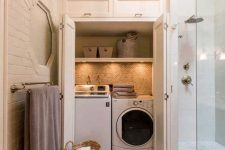 10 a welcoming neutral bathroom with a mini laundry hidden in a large cabinet, with built-in lights
