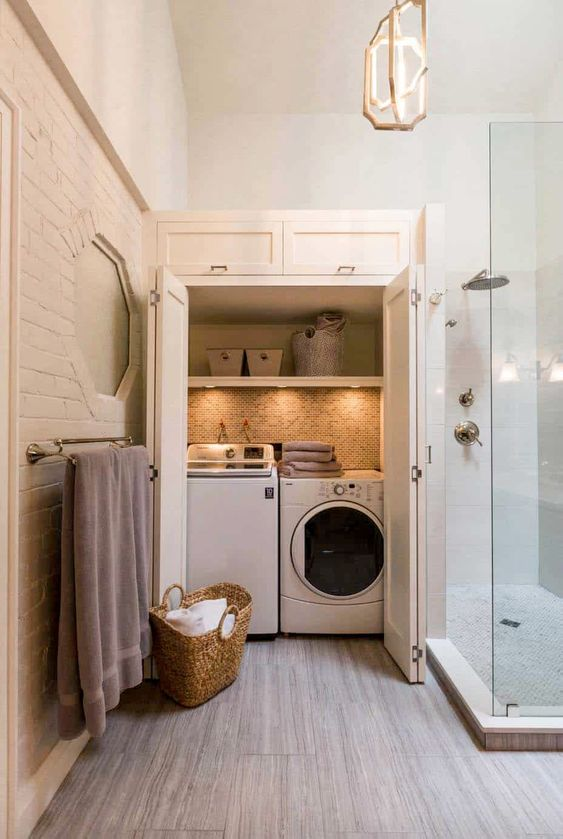a welcoming neutral bathroom with a mini laundry hidden in a large cabinet, with built in lights