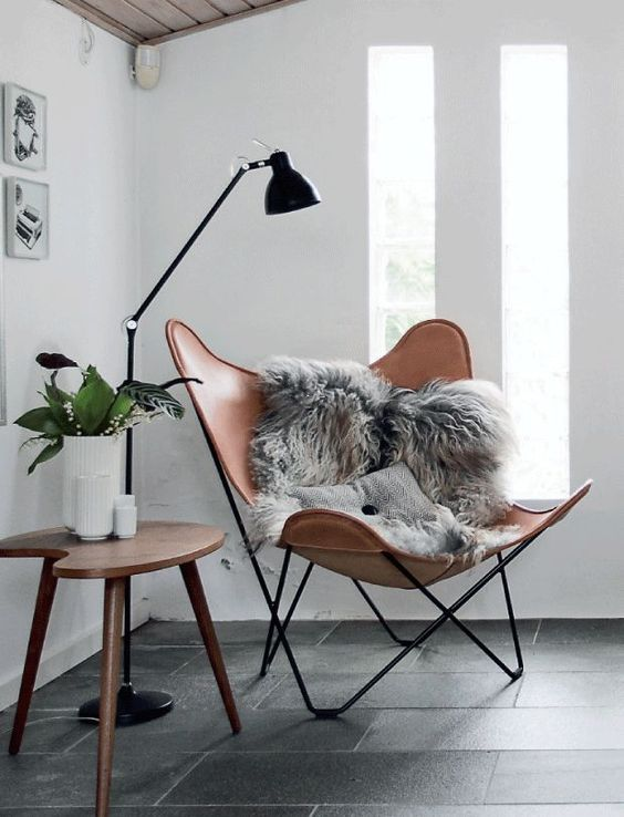 a brown leather butterfly chair, a stylish floor lamp and a cutout table for a chic Scandinavian reading nook
