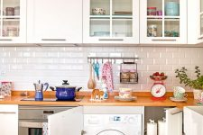 11 a cozy white kitchen with wooden countertops and a washing machine built into a cabinet is a brilliant idea
