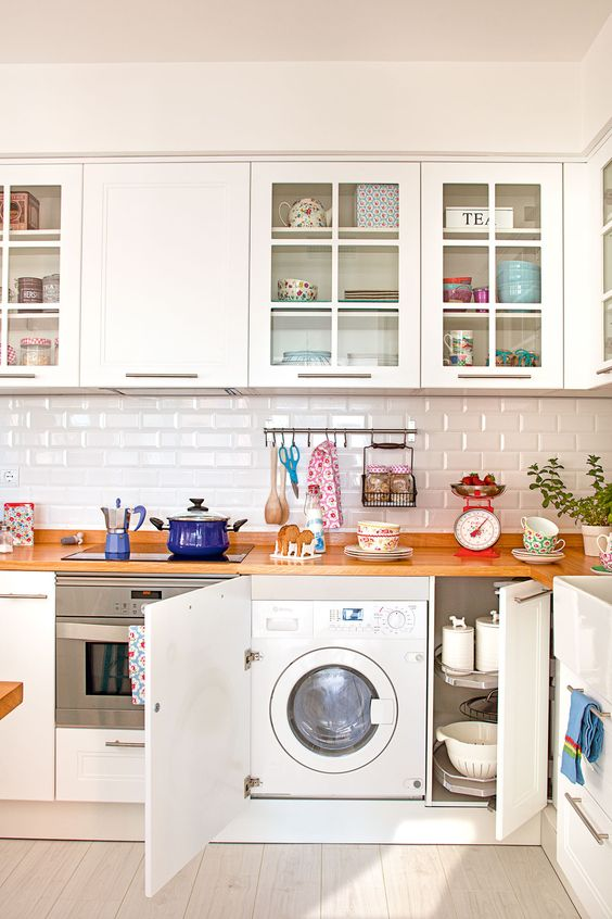 a cozy white kitchen with wooden countertops and a washing machine built into a cabinet is a brilliant idea