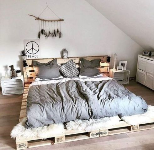 a simple low pallet bed with a headboard and whitewashed crate nightstands
