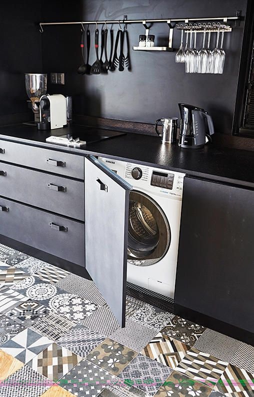 a modern black kitchen with a washing machine hidden in a cabinet is a stylish space-saving idea