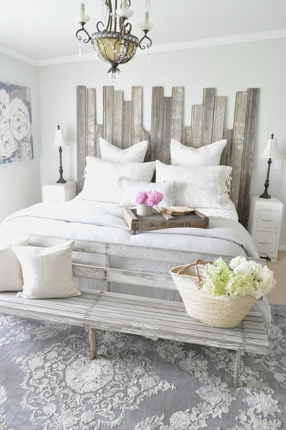 a shabby chic whitewashed headboard made of planks of different height