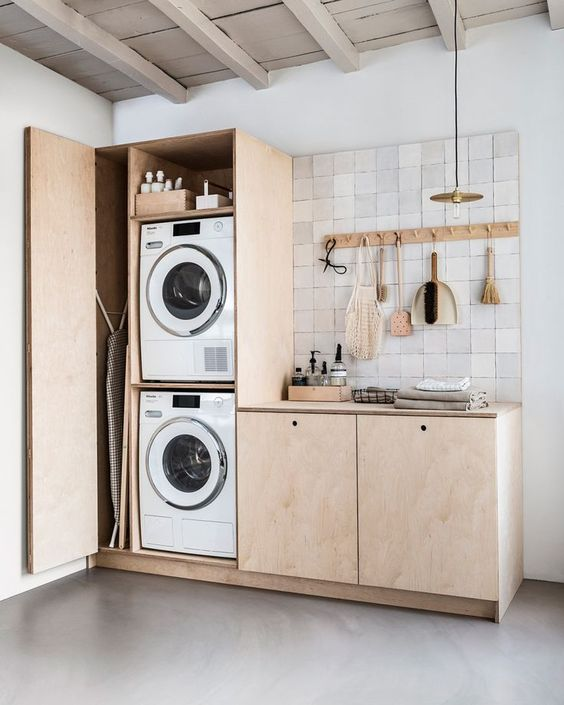 a small minimalist kitchen in neutrals, with a mini laundry hidden right here in the cabinet