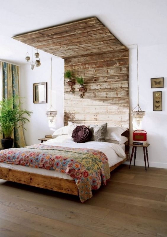 a weathered wood headboard that is extended to the ceiling to have a bigger impact