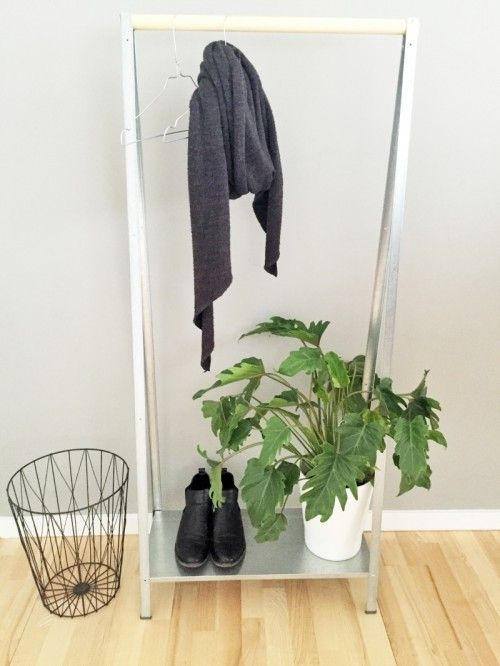 an IKEA Hyllis shelf turned into a simple and minimal entryway rack for hanging clothes and storing shoes
