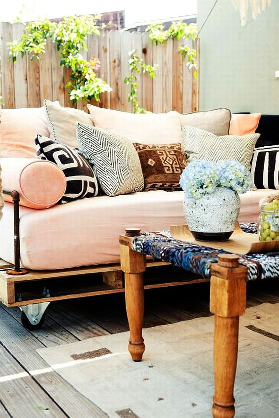 an outdoor pallet daybed on casters with a soft mattress and lots of colorful and printed pillows is heaven