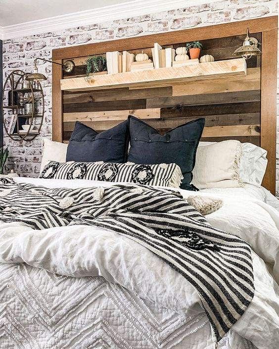 a farmhouse bedroom with a reclaimed wooden headboard that features a shelf with books, pumpkins and plants