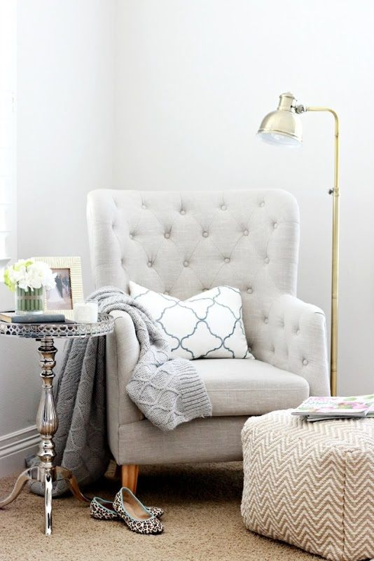 a grey tufted chair, a printed footrest, a floor lamp and a vintage refined side table for a chic reading nook