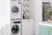 14 a small yet functional laundry hidden in the kitchen behind matching doors is a stylish hidden idea