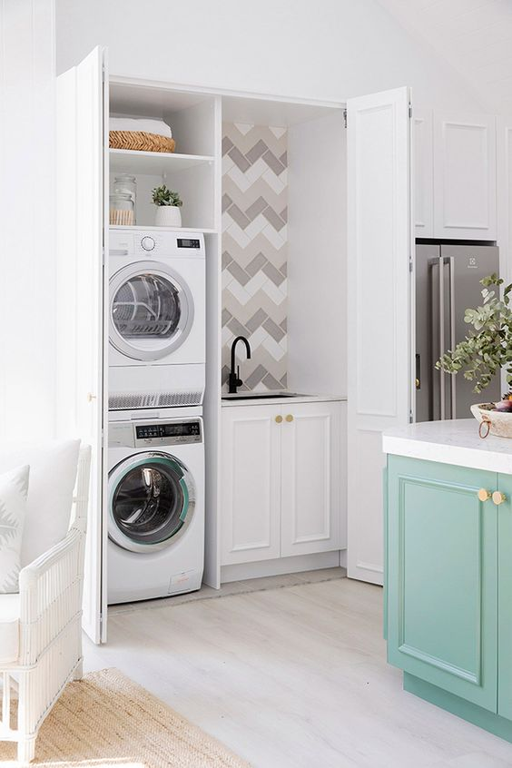 a small yet functional laundry hidden in the kitchen behind matching doors is a stylish hidden idea