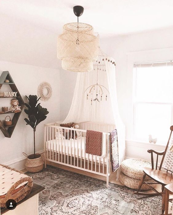 a boho farmhouse meets boho nursery with a statement wicker lamp, a printed rug, jute ottomans and a vintage rocker chairs