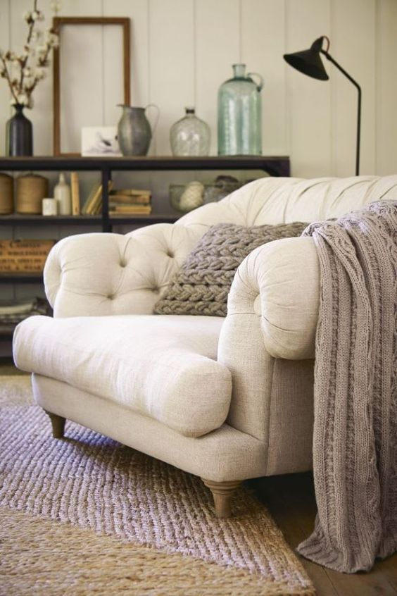 a large and comfy chair with neutral upholstery, a blanket and a floor lamp for perfect reading