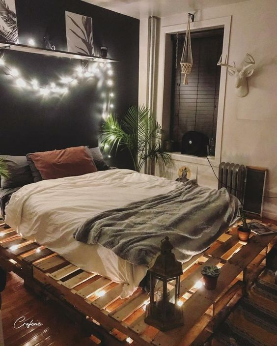 a modern boho bedroom with a black accent wall, a pallet bed with lights inside, lanterns and a statement plant