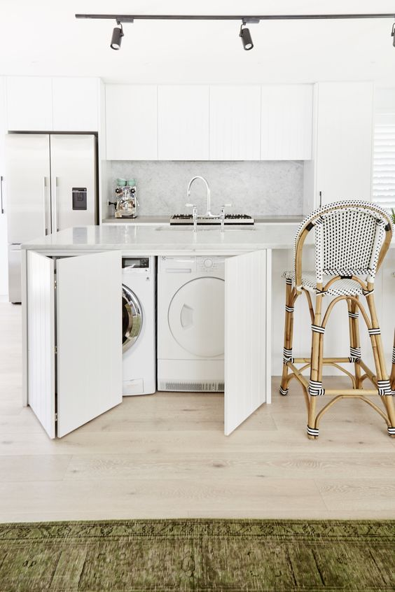 a white tropical kitchen with sleek minimalist cabinets and a washer and dryer hidden in the kitchen island
