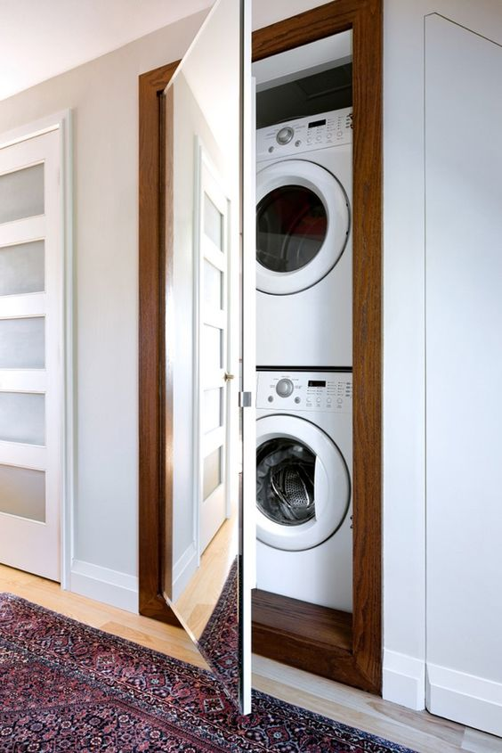 a built-in washer and dryer right in the wall, hidden with a floor to ceiling mirror is a very smart and modern idea