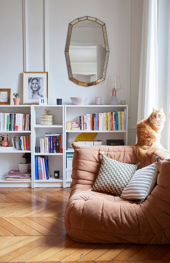 a modern rust-colored curved chair with pillows is a very stylish piece for reading and not only