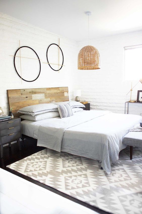 a serene modern bedroom with a reclaimed wooden headboard, a wicker pendant lamp and printed textiles