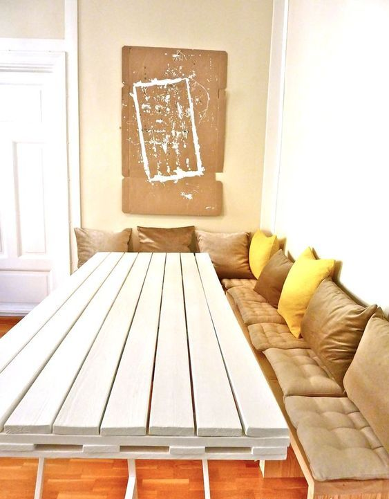 a white dining table with a tabletop made of a single pallet on thin metal legs is a stylish idea
