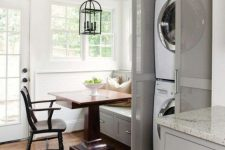 18 a farmhouse dining space with a washer and a dryer placed into a grey cabinet with semi sheer doors