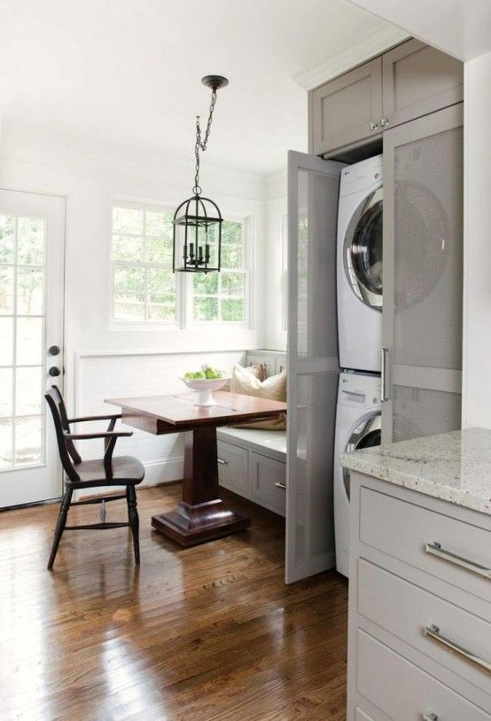 a farmhouse dining space with a washer and a dryer placed into a grey cabinet with semi sheer doors