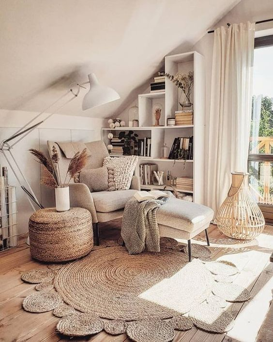 a neutral chair with pillows and blankets plus a footrest, jute rugs and a jute ottoman for a stylish boho reading nook