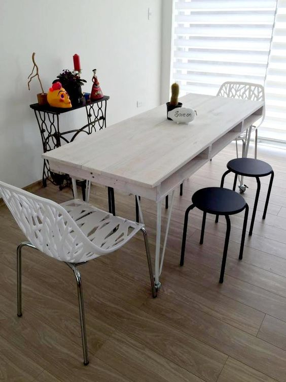 a whitewashed pallet dining table with a tabletop of a single pallet and thin metal legs on casters