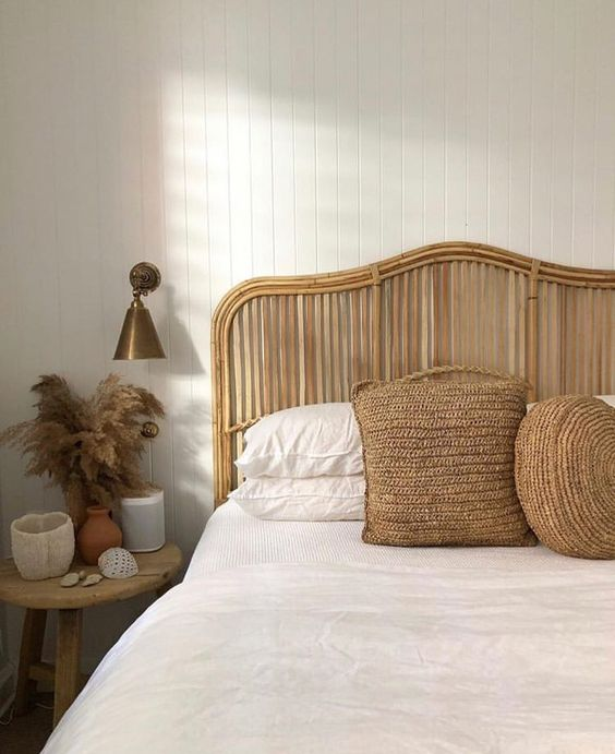 a boho headboard made of rattan and jute pillows give a summer feel to the space