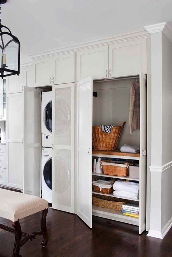 a mini laundry hidden in a closet behind semi sheer doors is a great way to keep it neat and not always seen