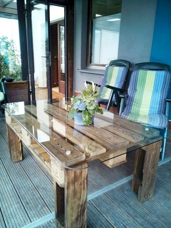 an outdoor contemporary meets rustic dining table of stained pallet wood and with a glass tabletop