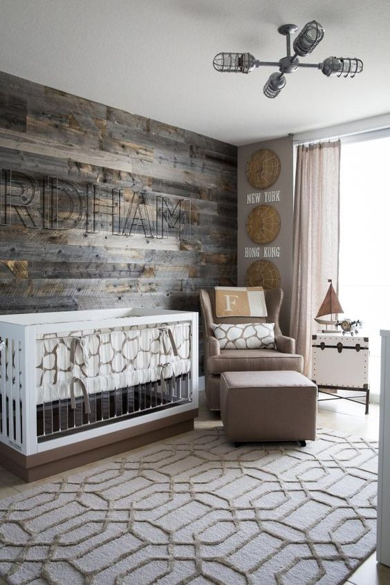 a farmhouse neutral nursery with a rough wooden wall, an acrylic crib, baskets on the wall and a taupe chair