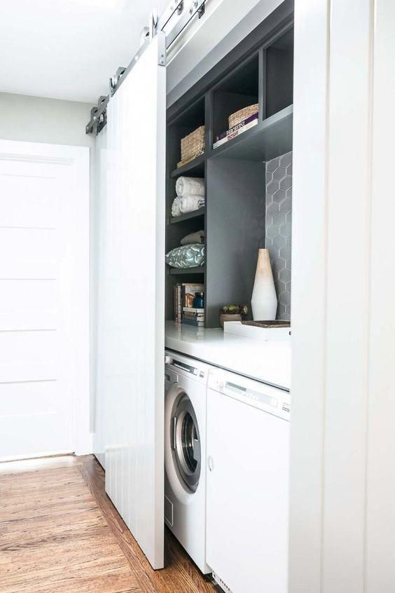 a mini laundry hidden in the entryway behind a barn white sliding door is a very modern idea