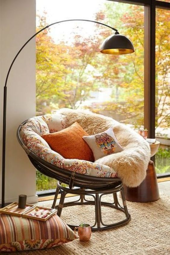 a rattan papasan chair with soft upholstery, faux fur and pillows, a floor lamp and bright pillows around for cozy reading