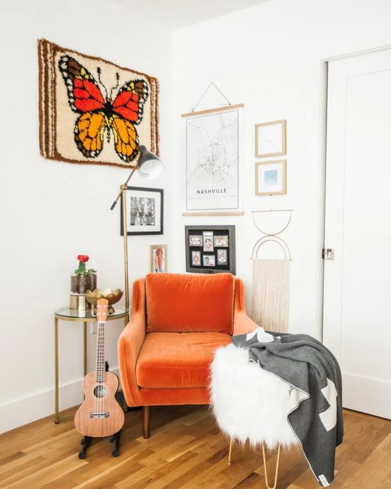 a bright orange velvet chair is a chic solution for a reading nook and it will add much color to the space