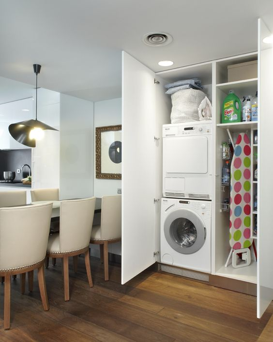 a mini laundry hidden right in the dining space in a large wardrobe is a great idea to try