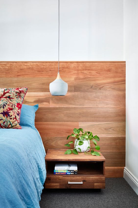 a sleek warm stained wooden headboard and a floating nightstand attached to it