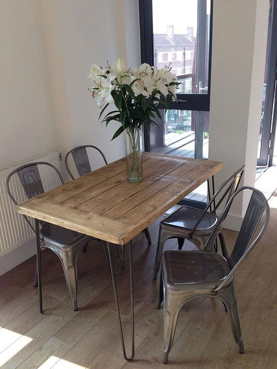 a small pallet dining table on hairpin legs and black metal chairs for a rustic industrial space