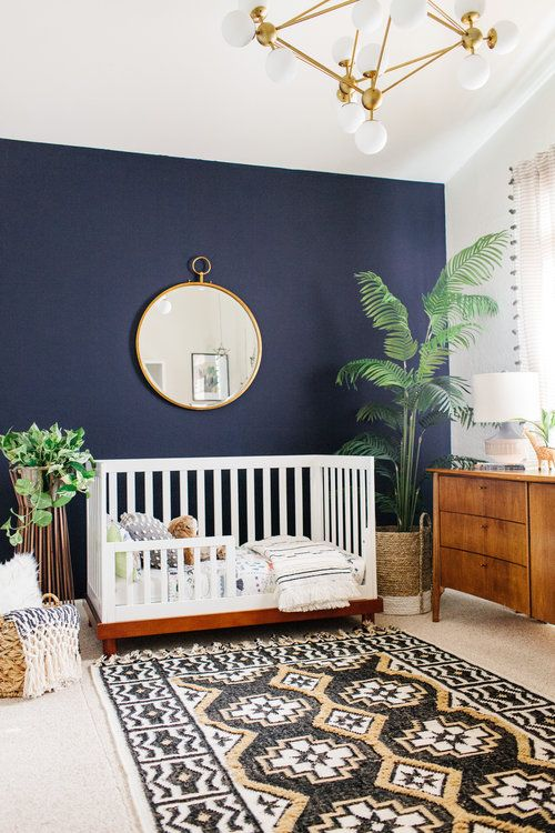 a stylish boho nursery with a navy accent wall, a white crib and a wooden sideboard, a printed rug and a round mirror plus statement plants