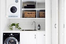 22 a monochromatic laundry hidden with folding doors somewhere in a mudroom or entryway