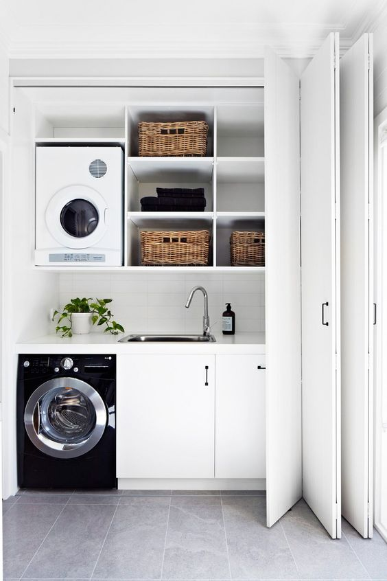 a monochromatic laundry hidden with folding doors somewhere in a mudroom or entryway