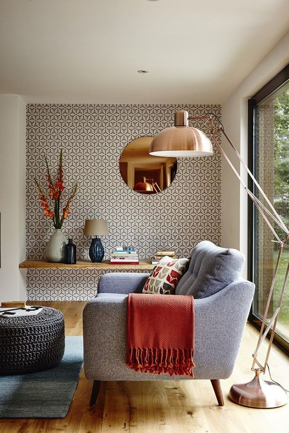 a stylish mid-century modern chair with a blanket and a cool floor lamp by its side are perfect for a reading nook