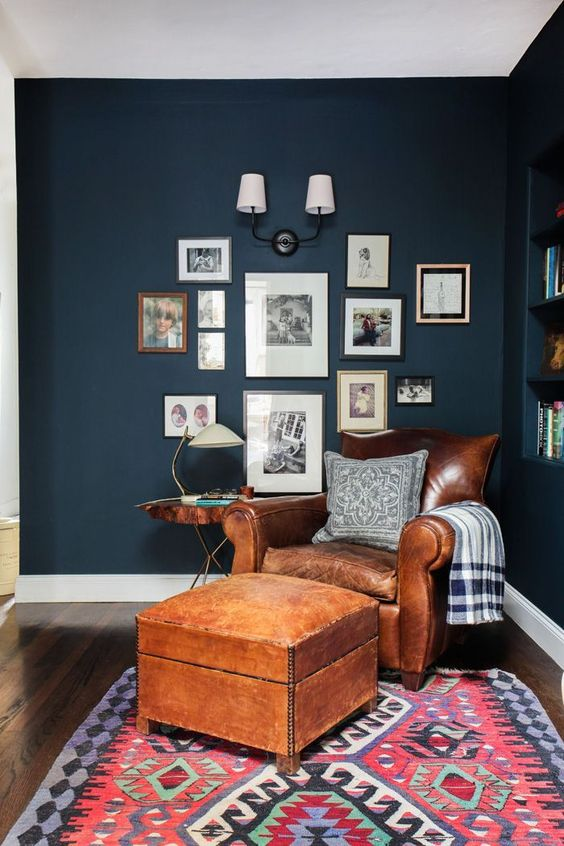 a traditional brown leather chair and a footrest, a gallery wall and a table lamp for a timelessly cozy reading nook