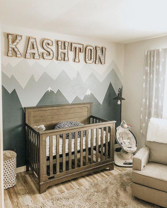 an adventuruous nursery with a mountain accent wall and a baby's name on the wall
